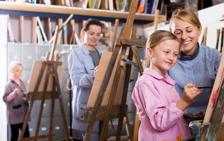 Female teacher helping girl during painting class