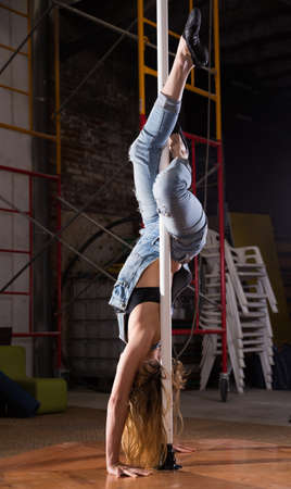 Young woman in ripped jeans performing pole dance