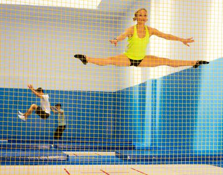Female gymnast jumping on trampoline