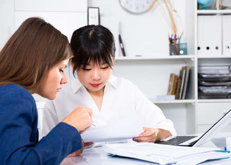 Asian woman working with client Banque d'images