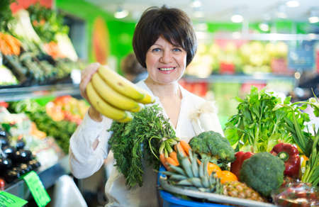 Adult female taking fruits and vegetables Imagens