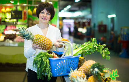 Middle aged woman with basket choosing pineapples