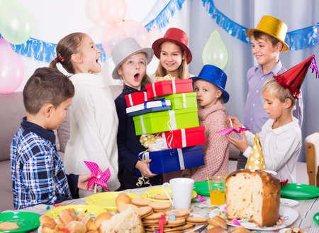 Glad children presenting gifts to girl birthday