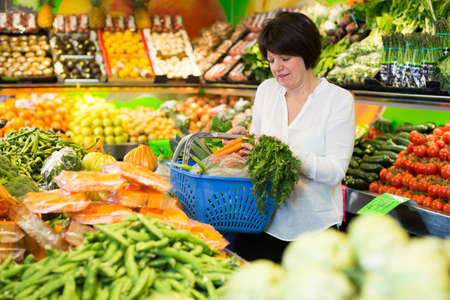 Mature woman buying fresh vegetables Imagens