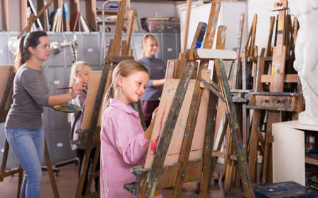 Female teenagers practicing their skills during painting class
