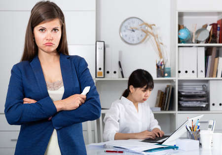 Frustrated woman standing at office