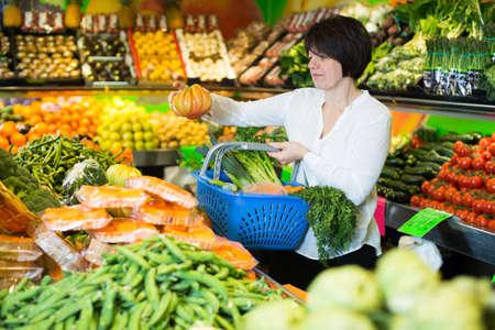 Adult female taking vegetables