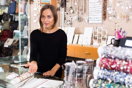Smiling seller female showing bracelets