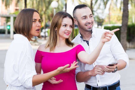 Young women are pointing the way to stranger man who was meet