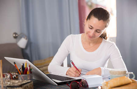 Young woman sitting at table at home calculating domestic finances