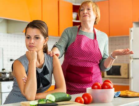 Upset young woman with mother reprimanding her 版權商用圖片