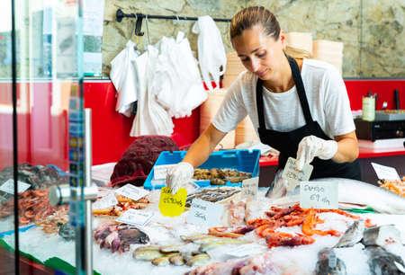 Woman fishmonger preparing display for sale