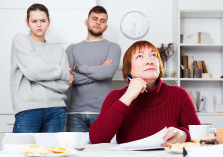 Frustrated senior woman with papers with discontented young couple