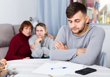 Frustrated man with papers on background with discontented family