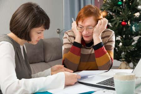 Adult daughter explaining document to upset elderly mother
