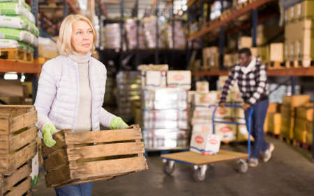 Woman carrying wooden boxes in store warehouse Stockfoto