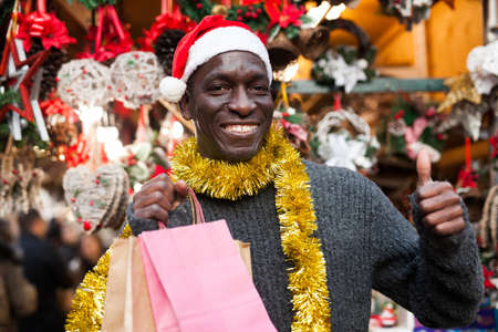 Laughing guy in Santa hat after Christmas shopping