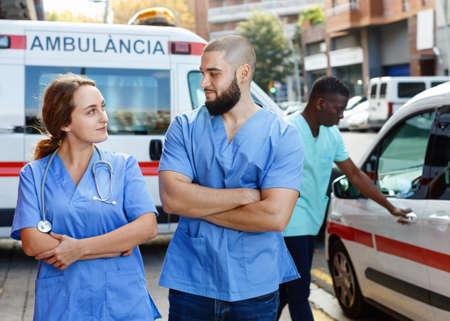 Two confident paramedicals in uniform posing near ambulance car