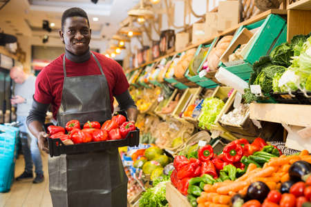 Seller arranging red peppers on greengrocery counter