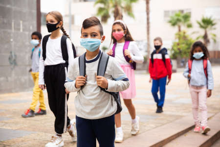 Hispanic tweenager in medical mask going to school lessons