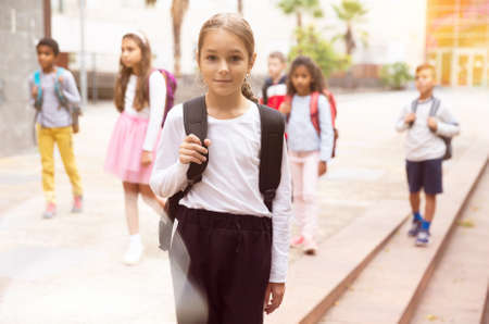 Teenage girl with backpack going to school on autumn day