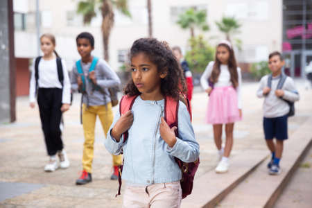 African american preteen girl walking to school on autumn day
