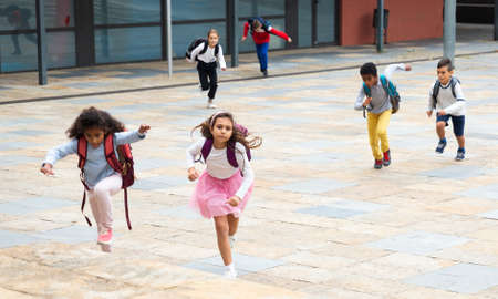 Group of cheerful tweenagers running in school yard after lessons Stockfoto