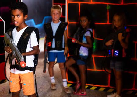 Two boy standing back to back with laser pistols