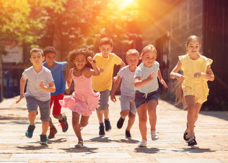 Cheerful active children are racing along the street