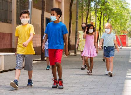 Schoolchildren in masks walking together on the street Banque d'images