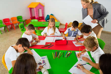 Female teacher helping schoolkids drawing with color pencils in classroom Banco de Imagens