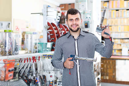cheerful male customer examining various glue guns in store Banco de Imagens