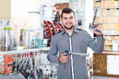 cheerful male customer examining various glue guns in store Imagens
