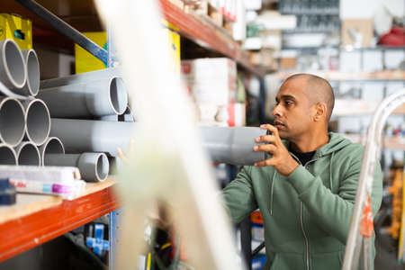 Hispanic man looking for construction supplies in building hypermarket 版權商用圖片
