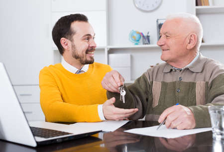 Old man and agent sign lease contract Banque d'images