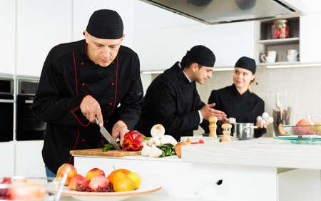 Team of woman and man chefs in black uniform preparing food Foto de archivo