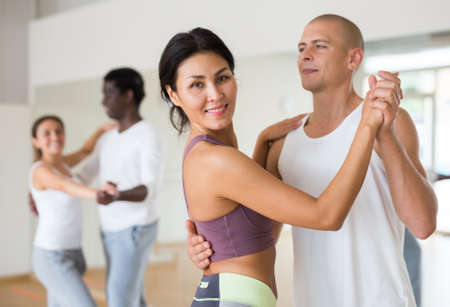Smiling asian woman learning to dance waltz with partner