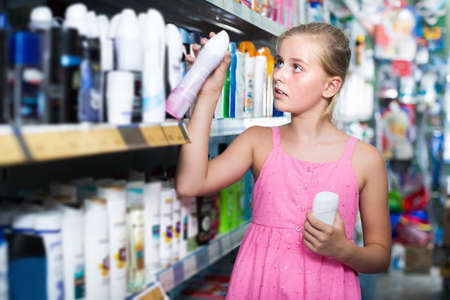 Young girl holding body spray in the hand