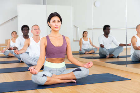 Young people meditating together at yoga class