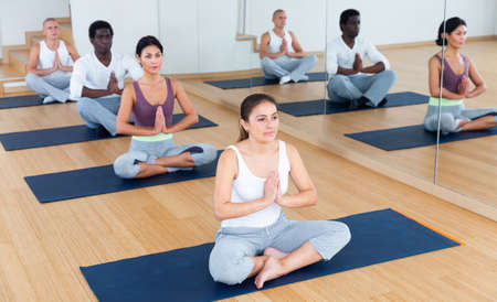 Sporty people meditating in yoga position Padmasana at gym