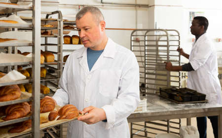 Baker putting tray with bakery goods on trolley