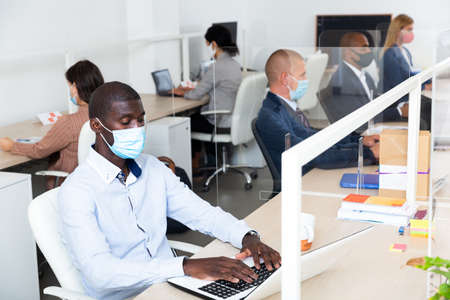 Focused afro american businessman in medical mask working in office