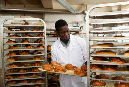 African baker placing tray with baked rolls on trolley