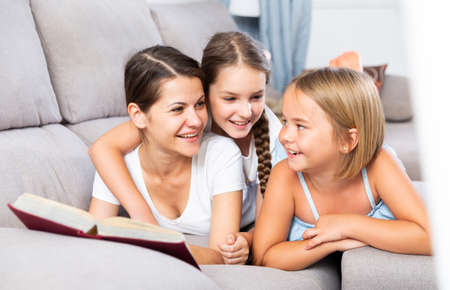 Woman reading book to daughters on sofa Stockfoto