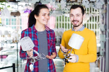 couple discussing purchase of night lamp Фото со стока