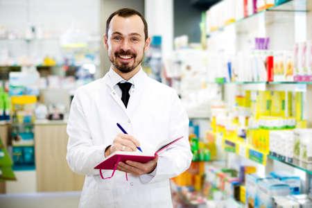 Male pharmacist checking assortment of drugs