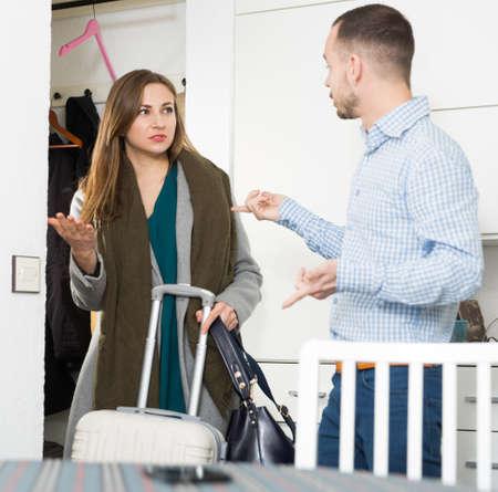 Man arguing with girlfriend at doorway