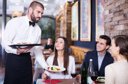 waiter man serving company at restaurant