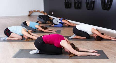 Women exercising yoga poses in fitness center
