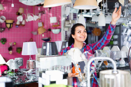 Girl in lighter shop chooses stylish and modern chandelier lamp